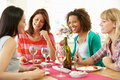 Group of women sitting around table eating dessert whilst chatting to each other smiling Royalty Free Stock Photography