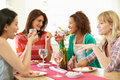 Group of women sitting around table eating dessert whilst looking at each other talking Royalty Free Stock Photo