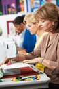 Group of women using electric sewing machines in class smiling Stock Photo