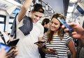 Group of young adult friends using smartphones in the subway Royalty Free Stock Photo