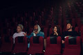 Group of young adults watching movie in theater