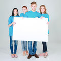 Group of young friends holding a blank board, isolated on white background Royalty Free Stock Photo