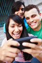 Group of young friends laughing at cellphone Stock Photos