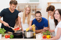 Group of young friends preparing pasta diverse standing around the stove cooking spaghetti and a tomato based sauce Royalty Free Stock Photography