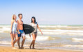 Group of young happy friends with surfboard at the beach on vacations holding a people having fun in summer boogieboard during Royalty Free Stock Photography