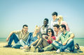 Group of young hipster best friends with digital tablet sitting at the beach concept multi cultural friendship against racism Royalty Free Stock Images