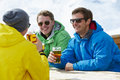 Group Of Young Men Enjoying Drink In Bar At Ski Resort Royalty Free Stock Photo