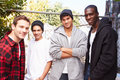 Group of young men in urban setting standing by fe fence smiling at camera Royalty Free Stock Image