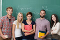 Group of young multiethnic students college or university standing in a row in front a blackboard with cheerful friendly smiles Royalty Free Stock Photo
