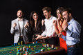 Group of young people behind roulette table on black background Royalty Free Stock Photo