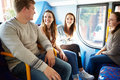Group of young people on bus journey together sitting down chatting to each other Royalty Free Stock Photography