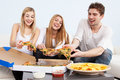 Group of young people eating pizza at home Stock Photos