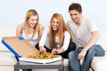 Group of young people eating pizza at home Royalty Free Stock Photography