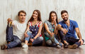 Group of young people four attractive friends sitting on the floor keeping beer in hands smiling looking into the camera Royalty Free Stock Photos