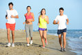 Group of young people running in the sand on the shore of a beach by the sea at sunset during a sunny summer holiday vacation Royalty Free Stock Photo