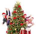 Group young people in santa hat showing thumb up by christmas tree Royalty Free Stock Image