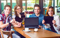 Group of young people sitting at a cafe, holding electronic gadgets