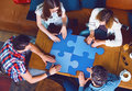 Group of young people sitting at a cafe, holding a puzzle pieces Royalty Free Stock Photo