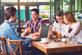Group of young people sitting at a cafe, talking Royalty Free Stock Photo