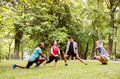 Group of young runners stretching and warming up in park. Royalty Free Stock Photo