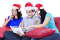 Group of young teenager drinking champagne in santa hat and using a tablet Royalty Free Stock Images