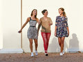 Group of young women leisure freetime walking on city street against wall Royalty Free Stock Images