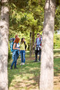 Group of youngsters in woods hiking among trees Royalty Free Stock Images