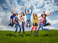 Groupe of jumping happy teenage friends on the green meadow Royalty Free Stock Image