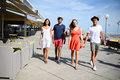 Groupe of young people man and woman walking on seaside of touristic resort during sunny summer day Royalty Free Stock Photo