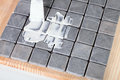 Grout worker applies at grey tiles Stock Photography
