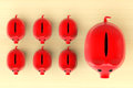 Growing investment concept red piggy banks in row on a wooden table Royalty Free Stock Photography