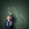 Growing up taller than a dinosaur young boy measuring his growth in height against blackboard with chalk scale Stock Image