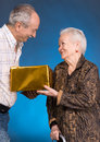 A grown son and aging mom with present box on blue background Royalty Free Stock Photography