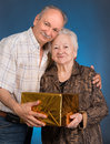 A grown son and aging mom with present box on blue background Royalty Free Stock Images