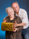 A grown son and aging mom with present box on blue background Stock Photography
