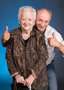 A grown son showing ok with his aging mom on blue background Royalty Free Stock Photo