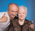 A grown son showing ok with his aging mom on blue background Stock Images