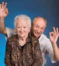 A grown son showing ok with his aging mom on blue background Royalty Free Stock Images