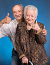 A grown son showing ok with his aging mom on blue background Stock Photo
