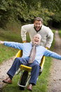 Grown up son pushing father in wheelbarrow Royalty Free Stock Photo