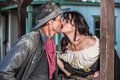 Gruff man and woman kiss portrait of an old west women sheriff kissing Stock Photos