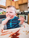 Grumpy child eats a breakfast in the kitchen Royalty Free Stock Photo