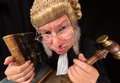 Grumpy judge old in extreme wide angle closeup with hammer and wig Stock Photo