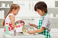 Grumpy kids doing home chores washing dishes on parents order Royalty Free Stock Photos