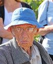 Grumpy old man photo of a pulling a face and wearing a blue summer hat photo ideal for facial expressions elderly people clothing Stock Images
