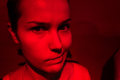 Grumpy woman portrait in red light of a displeased young Stock Photography
