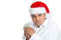 Grumpy young man in santa s hat possessive about his money closeup portrait of greedy miserly wearing red claus holding and Stock Image