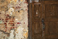 Grunge background - mangy wall with cracks, old wooden door Royalty Free Stock Photo