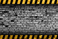 Grunge grey brick wall background with warning stripes Royalty Free Stock Photo