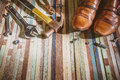 grunge leather shoes and many variety tools on wood background Royalty Free Stock Photo